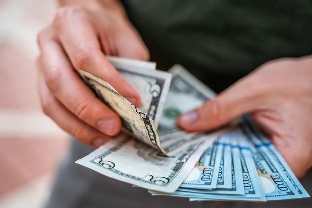 한 남자가 지폐 더미를 닫습니다.