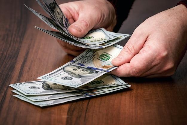 Мужчина считает деньги. валютные операции в банковском секторе_