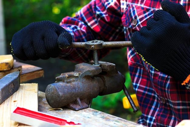 한 남자가 뒷마당에서 일하는 할아버지가 죔쇠로 고정되어 있는 볼트의 실을 자르고 있다.