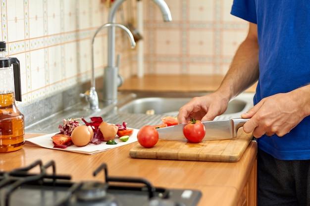 男がトマトを切る。台所で食べ物を準備している間の、食品廃棄物と端材。クローズアップ、セレクティブフォーカス