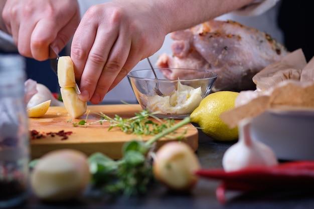 男が若いじゃがいもを切る。オーブンでハーブ、スパイス、レモンを使って鶏肉を調理するプロセス。