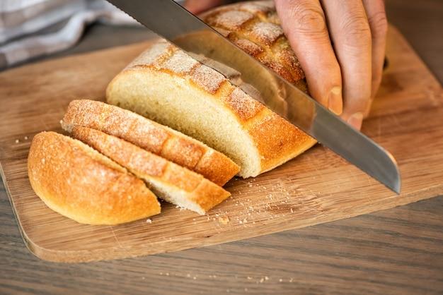 한 남자가 톱니 모양의 칼로 빵을 자릅니다.