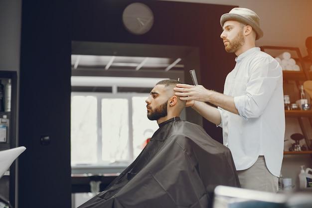 Мужчина режет волосы в парикмахерской