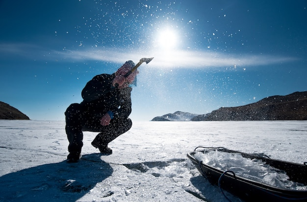 Человек зарубает лед топором на замерзшем озере байкал зимой