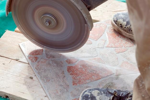 Мужчина резает напольную плитку