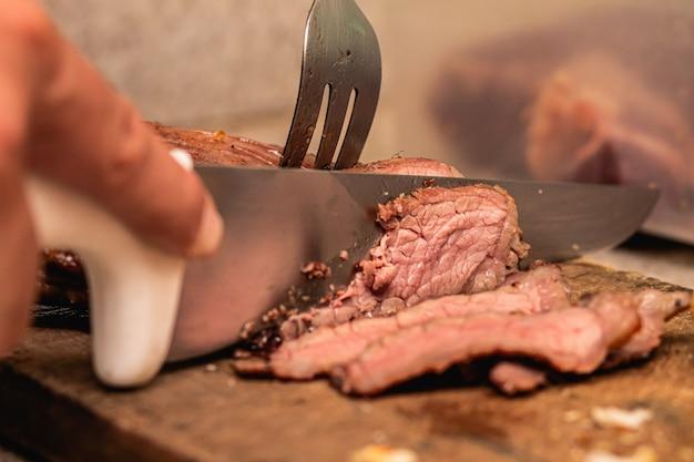 ナイフでブラジルのバーベキュー肉をポイントまで切る男