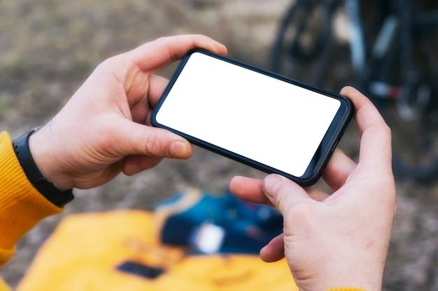 남자 사이클리스트는 자연 속에서 자전거의 배경에 그의 손에 흰색 화면이있는 스마트 폰의 모형을 보유하고 있습니다.