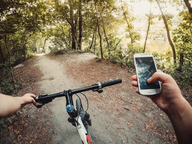 남자 자전거 타는 사람이 자전거를 타고 비포장 도로의 숲에 서서 손에 전화기를 들고 있습니다.