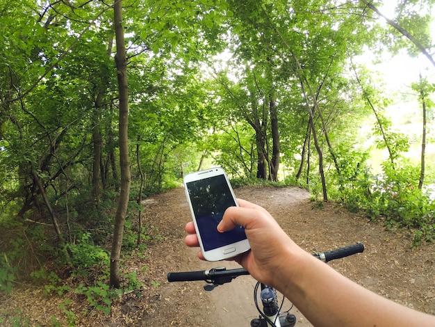 한 남자 자전거 타는 사람이 자전거를 타고 비포장 도로의 숲에 서서 손에 전화기를 들고 있다
