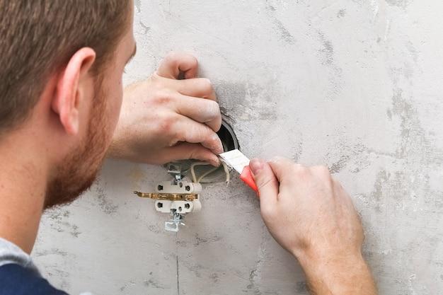 Мужчина разбирает и ремонтирует электрическую розетку