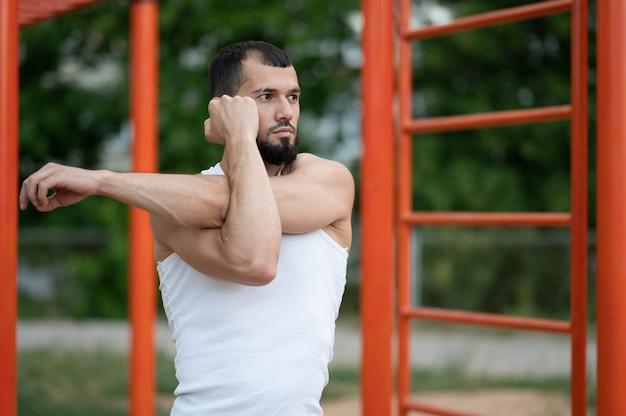 男は路上でトレーニングする前にウォームアップをします。トレーニング、トレーニング、ライフスタイル