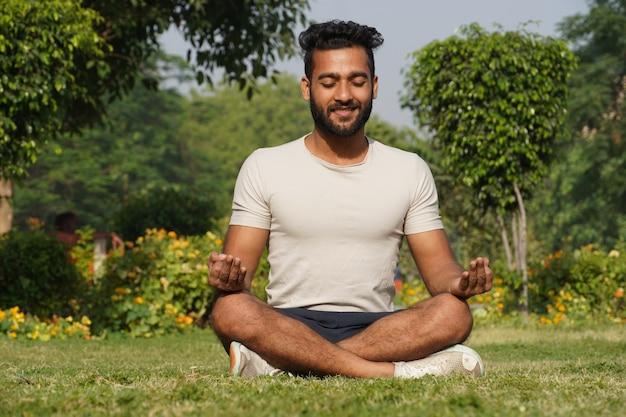 Мужчина занимается медитацией утром в парке