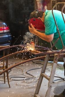 Мужчина занимается точечной сваркой под навесом своего гаража. разлетаются искры.