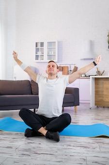 Мужчина делает упражнения йоги дома, сидя на полу в гостиной. здоровый образ жизни.