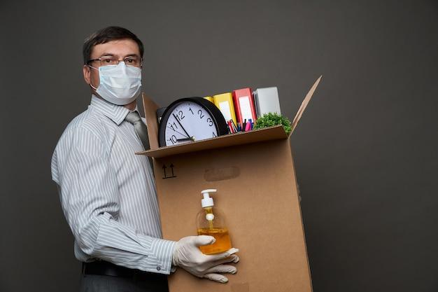 Мужчина в костюме бизнесмена держит коробку с офисными вещами.