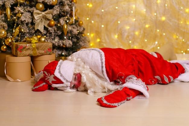 산타클로스 옷을 입은 남자가 선물을 들고 크리스마스 트리 옆 바닥에 누워 자거나 쉬고 있다