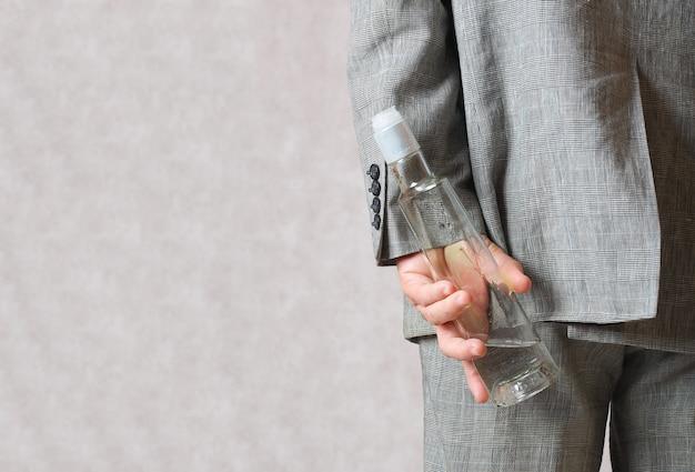 Мужчина в классическом костюме прячет за спиной бутылку спиртного