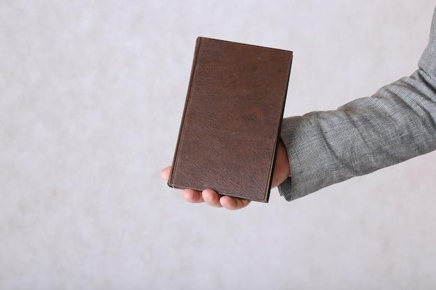 Мужчина в классическом костюме держит коричневую книгу. крупным планом