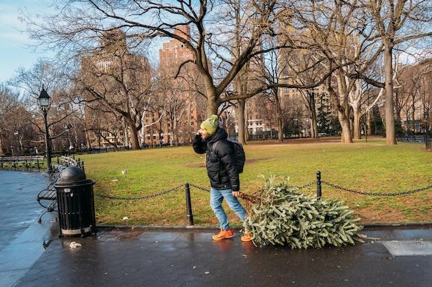 Мужчина в пальто тащит небольшую сосну, чтобы украсить ее на рождество, разговаривает по телефону