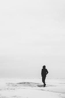 평범한 흰색 표면을 걷는 모든 검은 옷을 입은 남자