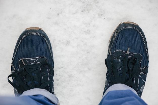 青いスニーカーを履いた男が雪の上に立っている