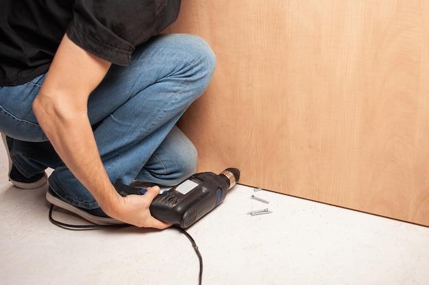 한 남자가 찬장 바닥에 드릴로 구멍을 뚫습니다.