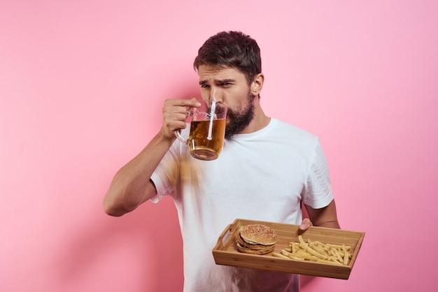 Мужчина пьет пиво из бокала и ест фаст-фуд, приготовленный из барахла