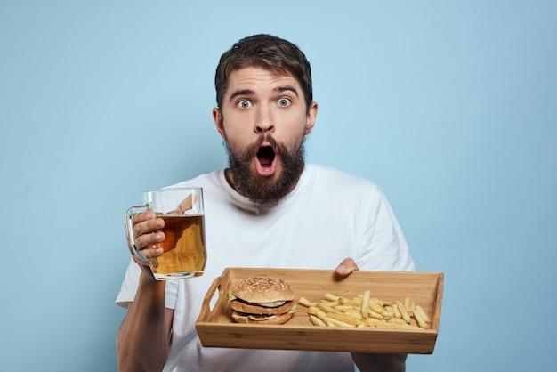 Мужчина пьет пиво из стакана и ест жареный фаст-фуд