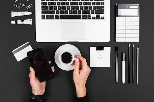 男は黒の背景に分離された彼のデスクトップでコーヒーを飲む