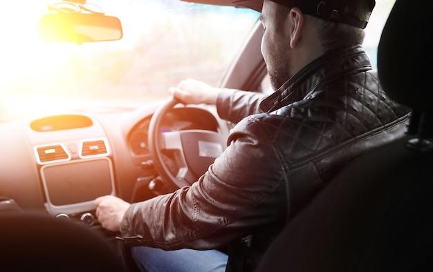 Мужчина водит машину. водитель едет на машине по дороге. солнце слепит водителя за рулем.