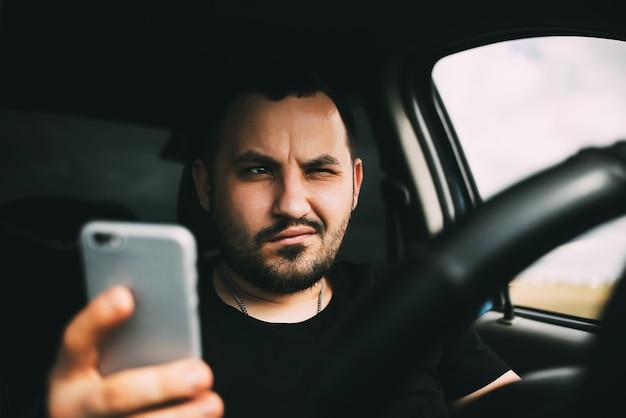 車を運転している男性がスマートフォンに気を取られた