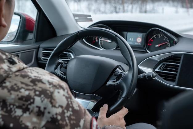 冬の道路で現代の車の中でハンドルを握って運転している男性