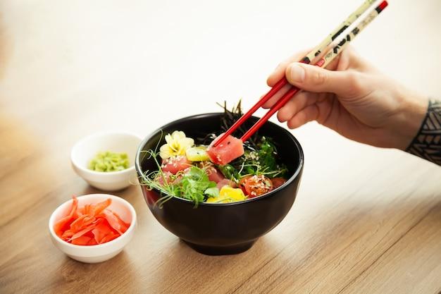남자는 젓가락으로 그릇에 참치와 포크 샐러드를 먹는다. 참치 샐러드를 그릇에 담습니다. 포케 샐러드를 먹고 레스토랑에서 젊은 남자 남자. 아시아 해산물 샐러드 개념입니다.