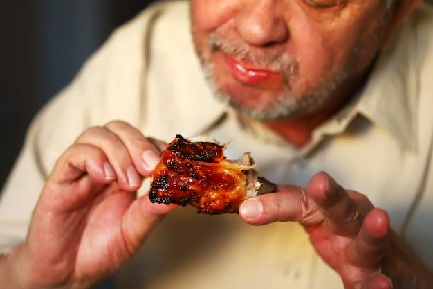 Мужчина руками ест запеченные свиные ребрышки. мужчина ест мясо. фастфуд. жареное мясо, конераген.