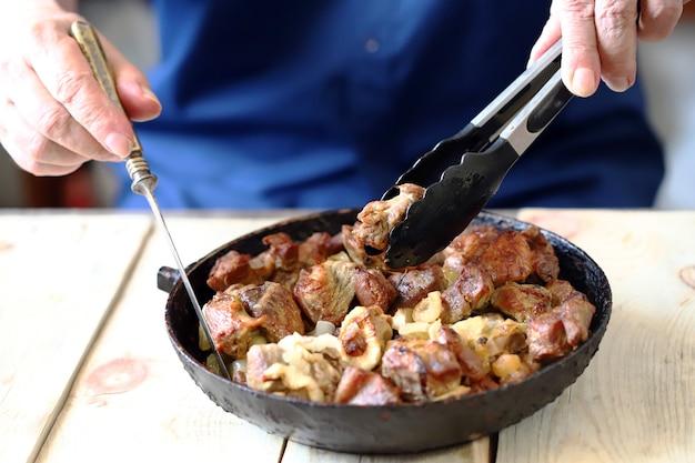 男はフライパンから肉片を食べる
