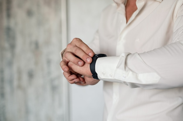男性のエレガントなビジネスマンは彼の手に時計をボタンで留めます彼は白いドレスシャツを着ています