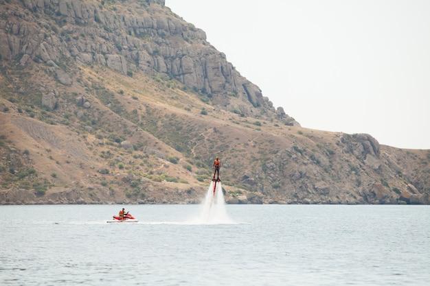 Мужчина занимается флайбордингом на берегу океана.