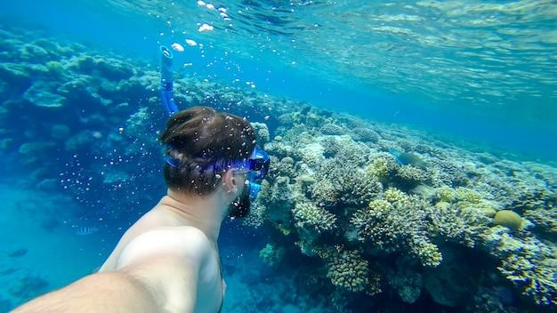 シュノーケリングをしている男性が紅海の底に潜り、珊瑚を背景に自分の写真を撮ります