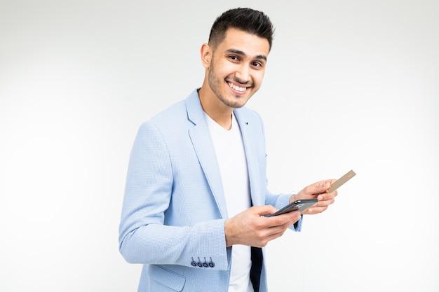 Мужчина вводит данные с кредитной карты в мобильный телефон, чтобы совершить покупку через интернет на белом фоне.