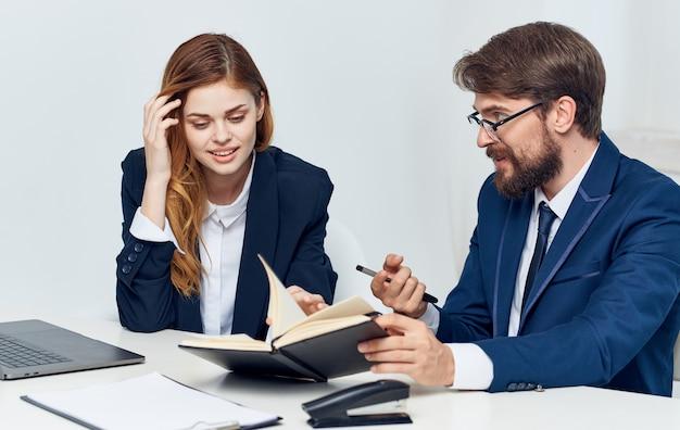 Мужчина что-то объясняет молодой женщине с ноутбуком в руке и ноутбуком с финансами для бизнеса. фото высокого качества