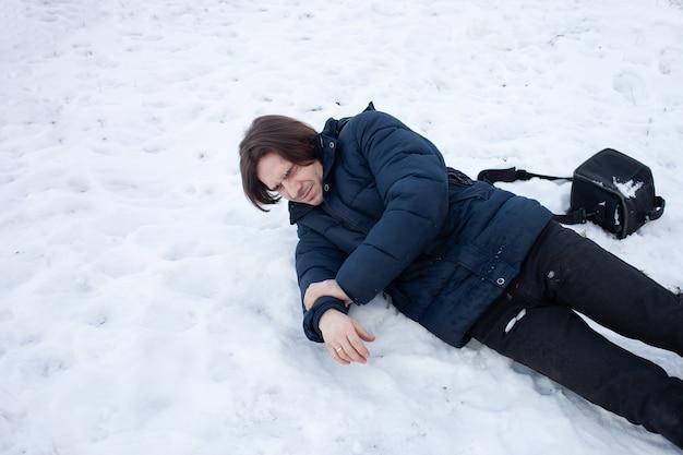 男が雪に落ちる。男は滑ってけがをした