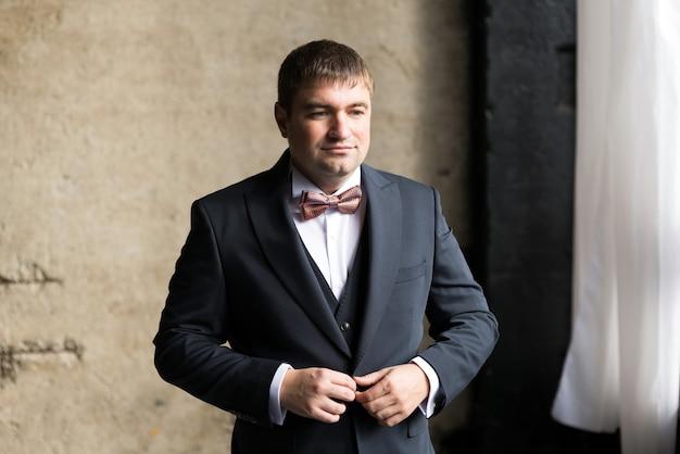 Мужчина застегивает пуговицы в деловом костюме