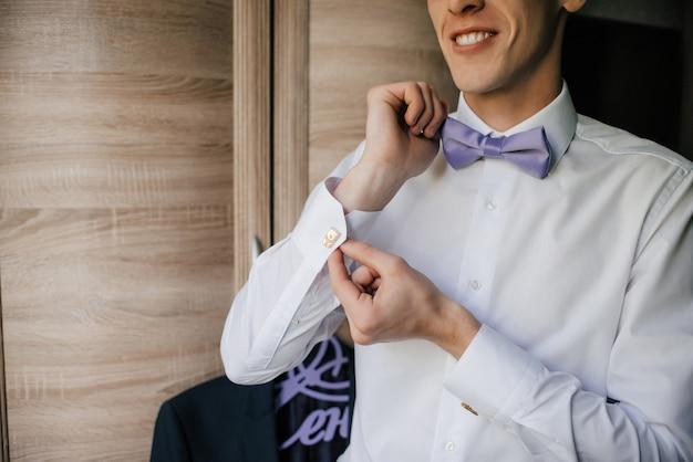 Мужчина застегивает запонки на белую рубашку