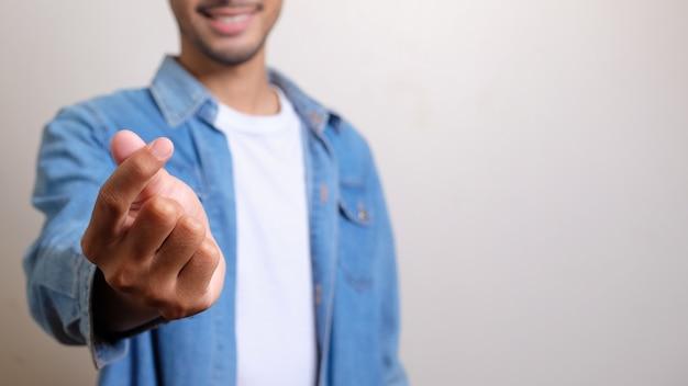 남자는 행복을 느끼고 긴장을 풀고 흰색에 심장 형태로 손가락을 만듭니다.