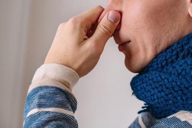 男が鼻をつまんで気分が悪くなる喉がスカーフで結ばれる