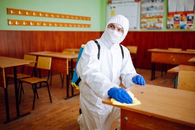 Мужчина из группы дезинфекции чистит парту в школе желтой тряпкой. профессиональный работник стерилизует класс, чтобы предотвратить распространение covid-19. концепция здравоохранения школьников и студентов.