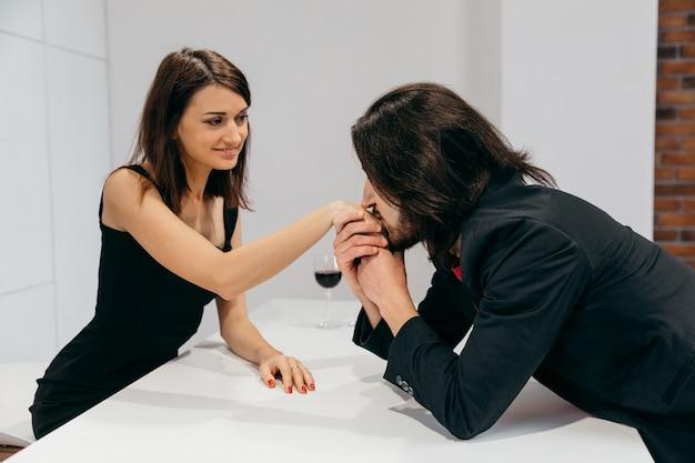 한 남자가 청혼 후 사랑하는 여자의 손에 부드럽게 키스합니다. 고품질 사진