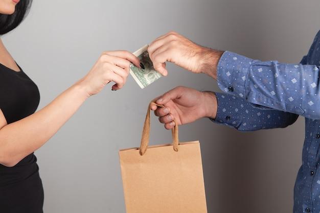 남자는 선물 가방을 주고 여자는 그것을 지불합니다. 쇼핑 개념