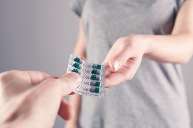 Мужчина протягивает девушке таблетку в руку