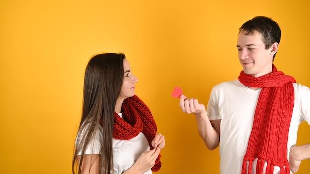 Мужчина дарит сердце женщине на желтом